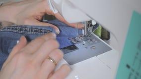 Een vrouw naait op een naaimachine stock footage