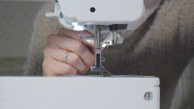 Een vrouw naait op een naaimachine stock videobeelden