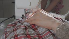 Een vrouw naait op een naaimachine stock video