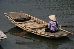 Een vrouw navigeert met een boot op een meer (Vietnam) Stock Foto