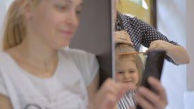 Een vrouw neemt beelden met haar smartphone aangezien een kapperstilist een kapsel voor een leuke kleine dochter in a maakt stock footage