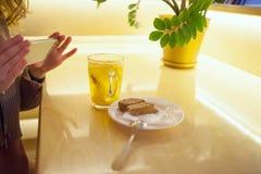 Een vrouw neemt beelden van voedsel met haar telefoon stock fotografie