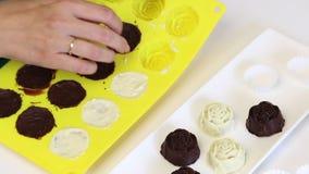 Een vrouw neemt kant-en-klaar suikergoed dat met zwart-witte chocolade van een siliconevorm wordt verglaasd stock video