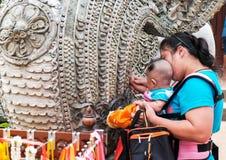 Een vrouw onderwijst haar kind voor eerbied de koning van naga bij de temperaturen Stock Foto's
