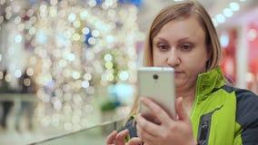 Een vrouw onderzoekt een smartphone in verrassing, bevindt zij zich in een winkelcentrum, tegen een achtergrond van een gloeilamp stock footage