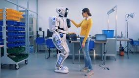 Een vrouw ontmoet een robot in een ruimte De robot en de vrouw geven elkaar hoog-vijf, dan kopieert een droid haar bewegingen met stock video