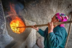 Een vrouw ontsteekt een tandoor - een traditionele Oezbekistaanse oven Stock Foto