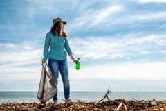 Een vrouw op de vooravond van de Dag van de vakantieaarde verleent vrijwilligershulp in het schoonmaken van het kustgebied van pu stock foto's