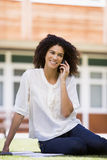 Een vrouw op haar mobiele telefoonzitting in openlucht Stock Foto