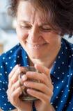 Een vrouw op middelbare leeftijd in de koffie houdt een kop van hete thee in haar Ha stock fotografie