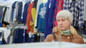 Een vrouw op middelbare leeftijd in een de winterlaag en een hoed gaat naar een de kledingsopslag van kinderen Bekijkt de planken stock footage