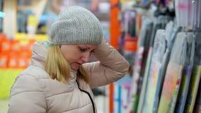 Een vrouw op middelbare leeftijd in een hoed en een benedenjasje kiest goederen in de supermarkt stock footage