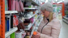 Een vrouw op middelbare leeftijd in een hoed en een benedenjasje kiest een rode thermosfles in een supermarkt stock video