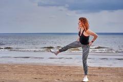 Een vrouw op middelbare leeftijd met rood haar doet gymnastiek op de zandige kust van een grote rivier royalty-vrije stock foto's