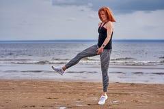 Een vrouw op middelbare leeftijd met rood haar doet gymnastiek op de zandige kust van een grote rivier royalty-vrije stock foto