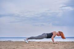 Een vrouw op middelbare leeftijd met rood haar doet gymnastiek op de zandige kust van een grote rivier stock afbeelding