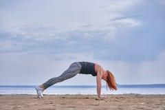 Een vrouw op middelbare leeftijd met rood haar doet gymnastiek op de zandige kust van een grote rivier royalty-vrije stock afbeeldingen