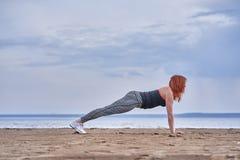 Een vrouw op middelbare leeftijd met rood haar doet gymnastiek op de zandige kust van een grote rivier stock fotografie