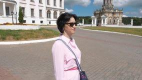 Een vrouw op middelbare leeftijd in een roze overhemd en blauwe broeken loopt rond de historische plaats stock video