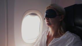Een vrouw op middelbare leeftijd slaapt in de cabine van een lijnvliegtuig, is een donker verband gekleed voor haar ogen stock video