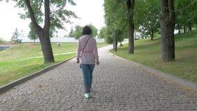 Een vrouw op middelbare leeftijd in zonnebril loopt langzaam in het park stock videobeelden