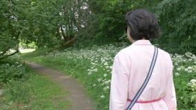 Een vrouw op middelbare leeftijd in zonnebril loopt langzaam in het park stock footage
