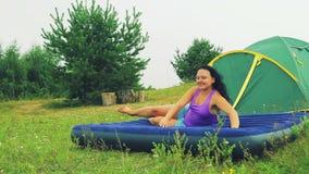 Een vrouw in een opheldering dichtbij de tent ligt op een opblaasbare matras stock videobeelden