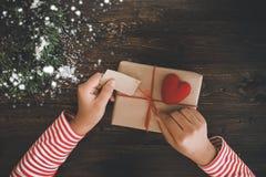Een vrouw overhandigt het uitstellen van een Kerstmisgift met een rood lint en sneeuw op een houten lijst Royalty-vrije Stock Foto