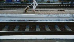 Een vrouw in een pak in een reiszak is op het station In het beeld kan slechts de benen en een zak worden gezien stock video