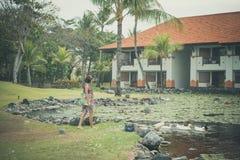 Een vrouw in pareo voedt grijze vertragingsganzen en gansjes op het meer dicht bij luxehotel in Nusa Dua, tropisch eiland van royalty-vrije stock foto's