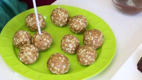 Een vrouw plakt een stok in een bal van pinda's en andere ingrediënten De spatie voor cake knalt Daarna op de plaat zijn kant-en- stock footage