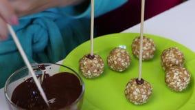 Een vrouw plakt een stok in een bal van pinda's en andere ingrediënten De spatie voor cake knalt Daarna op de plaat zijn kant-en- stock video