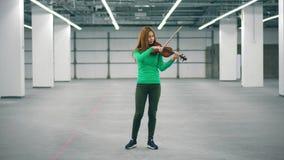 Een vrouw presteert in een bureauruimte, professioneel spelend viool stock videobeelden