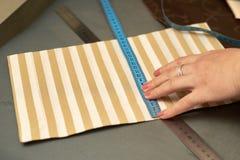Een vrouw probeert op gestreept materiaal alvorens openbaar royalty-vrije stock afbeelding