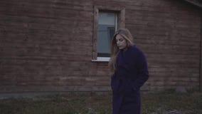 Een vrouw in een purpere laag loopt tegen de achtergrond van de manor met een venster stock videobeelden