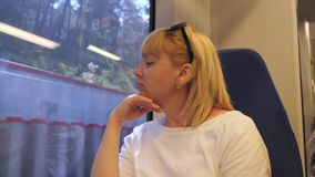 Een vrouw reist door trein De vrouwenzitting op de trein kijkt uit het venster Het concept toerisme en reis stock videobeelden