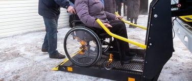 Een vrouw in een rolstoel op een lift van een gespecialiseerd voertuig voor gehandicapte mensen Taxi voor de gehandicapten Gele b stock afbeeldingen