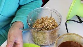 Een vrouw rolt een bal van het vullen voor suikergoed Neem de grondpinda's die met andere ingrediënten van de mixerkom worden gem stock video
