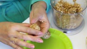 Een vrouw rolt ballen voor popcake het vullen en legt het op een plaat Van verpletterde die pinda's met andere ingrediënten worde stock video