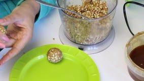 Een vrouw rolt ballen voor popcake het vullen en legt het op een plaat Van verpletterde pinda's die met andere ingrediënten worde stock footage