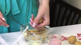 Een vrouw rolt koekjesballen want de cake knalt Dichtbij de lijst zijn glazen met suikerglazuur, stokken en klaar ballen op een p stock video
