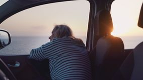 Een vrouw in een romantische stemmingsdromen bij zonsondergang op de oceaan stock videobeelden