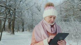 Een vrouw in een roze jasje geniet van een gang in een de winterpark Gebruikt een digitale tablet stock video