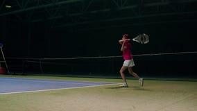 Een vrouw in een roze t-shirt en een wit begrenzen spelen van de ballen tijdens een tennisgelijke De tennisspeler leert te spelen stock video