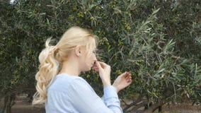 Een vrouw ruikt de olijf van een tak stock footage