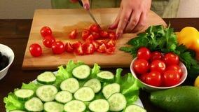 Een vrouw is scherpe kersentomaten om een plantaardige salade te maken stock footage