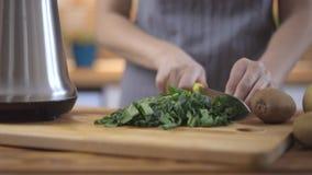 Een vrouw is scherpe spinazie op een keukenraad stock videobeelden