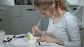 Een vrouw schildert paaseieren met gekleurde verven, close-up stock videobeelden