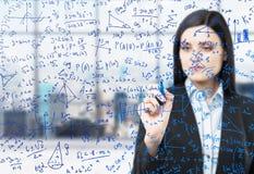 Een vrouw schrijft wiskundeformules in het glasscherm neer Modern panoramisch bureau met de mening van New York in onduidelijk be Stock Fotografie