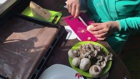 Een vrouw snijdt champignons op een scherpe raad De kaas ligt op een plaat naast het stock footage